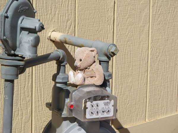 side view of garage exterior, including gas meter - on which sits a little stuffed bear