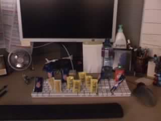 Packets of unopened mayo and mustard standing upright in my keyboard